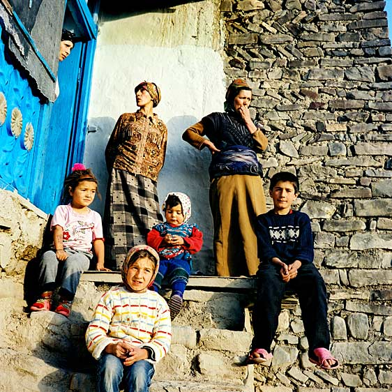 Family on a porch of their house. The houses in Xinaliq are built with the river stone as this is the easiest construction material to be found nearby. The old road to Xinaliq lead across several mountain rivers that become full and impossible to cross in fall and winter seasons. Access to the village in these seasons was blocked until a new road and bridges were built for the President's visit in late summer in 2006. Xinaliq village. Azerbaijan. June 2006