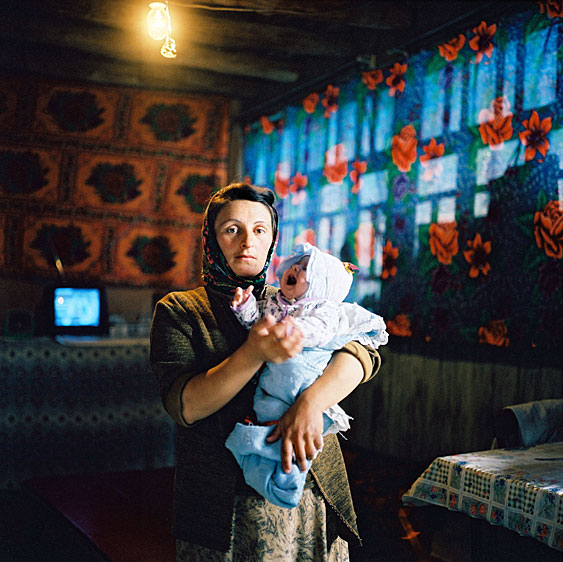 Woman holding a crying baby. The village has an intermittent supply of electricity, there is no water, sewage or gas supply. Women fetch water from springs and burn cow dung to cook. Xinaliq village. Azerbaijan. 2006