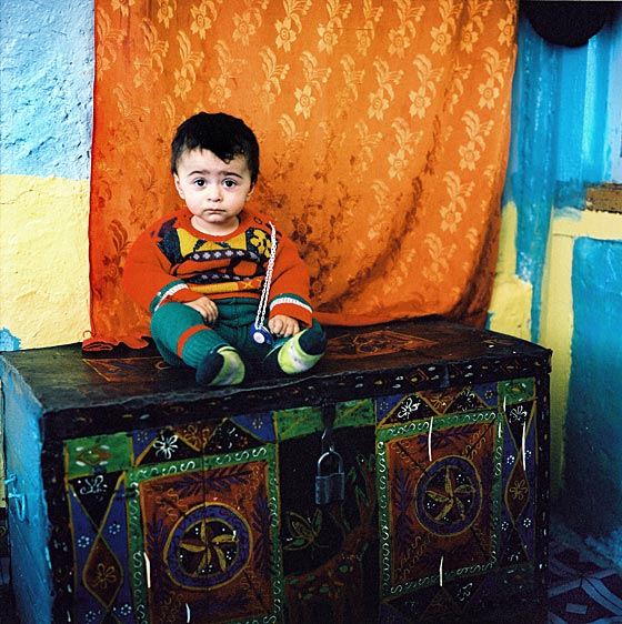 Toddler on a dowry chest. Xinaliq Village. Azerbaijan. June, 2006