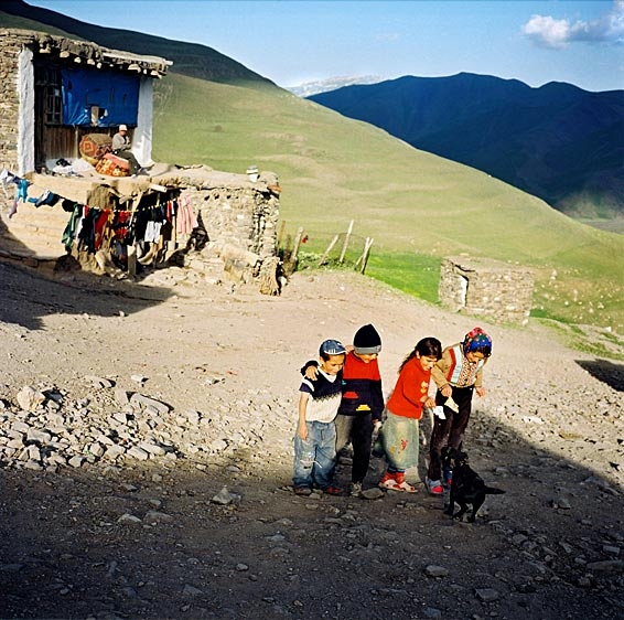 Children playing with a black puppy at the edge of the village. Xinaliq village. Azerbaijan. 2006
