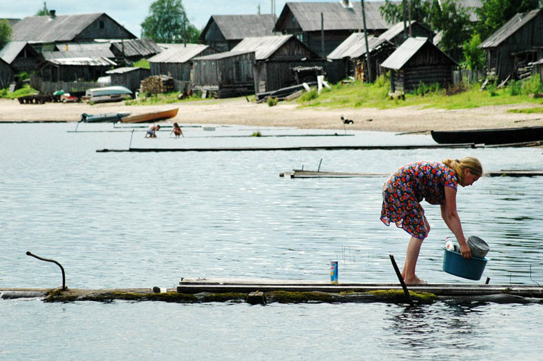 A woman washes dishes in Kenozero lake. There is no water supply or gas lines in the village houses.