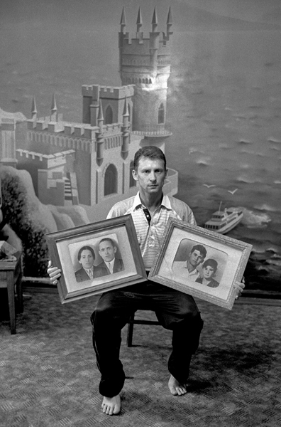 Portrait of Rustam Komurdzhi with photographs of his parents. Bahchisaray, August 2004.