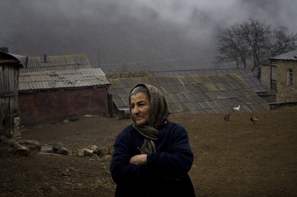 Nura Mirzoyan is standing near her house. She lost her son during the Karabakh war.