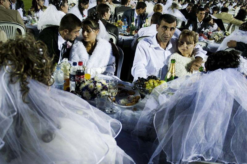 The couples were seated at rows of tables whilst the guests and relatives followed the event from spectator seats.