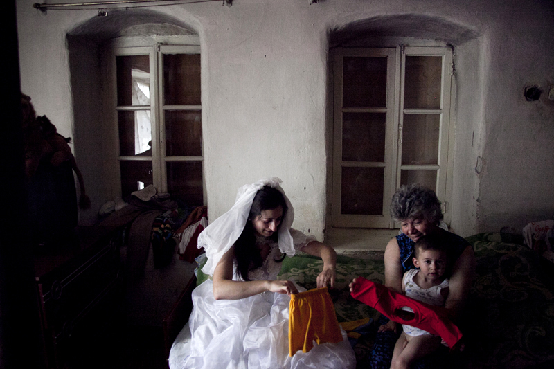 2011. Village of Khnatsakh. Anahit Grigoryan, 26, puts on her wedding gown and dresses up her 2 sons for a family portrait.