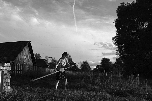 A woman with a scythe clears weeds from the garden of her village house. Village of Ivitsino, Yaroslav Region.