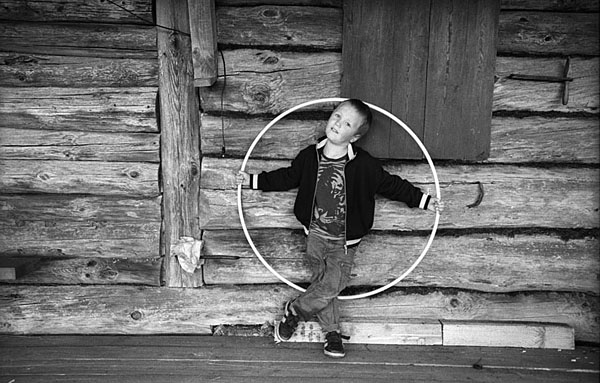 A young boy, Ilya, with a hoop at the house of his granmother Masha. Ivtsino village. Yaroslav Region.