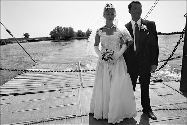 Bride and groom cross the Volga on a ferry on the river delta in Astrakhan.